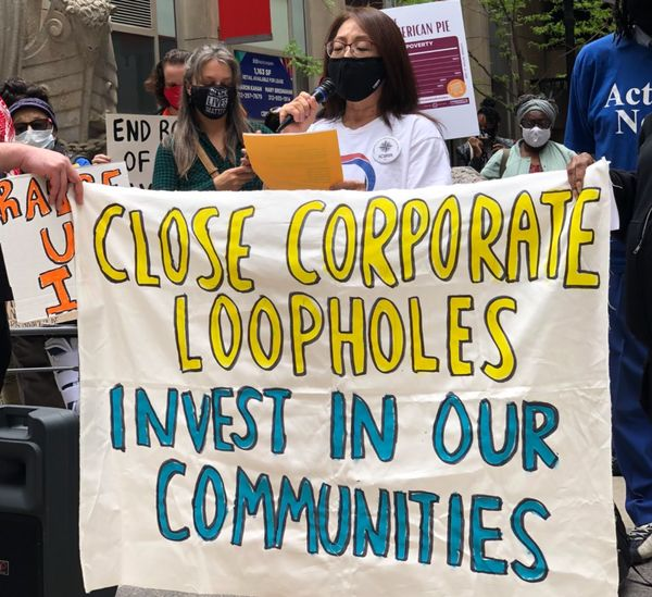 Group of Illinois residents holding banner reading close corporate loopholes.